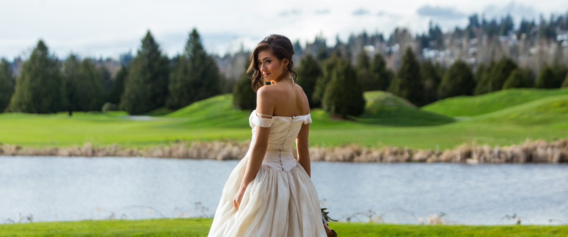 Bride posing for wedding photos overlooking the lake at the Golf Course