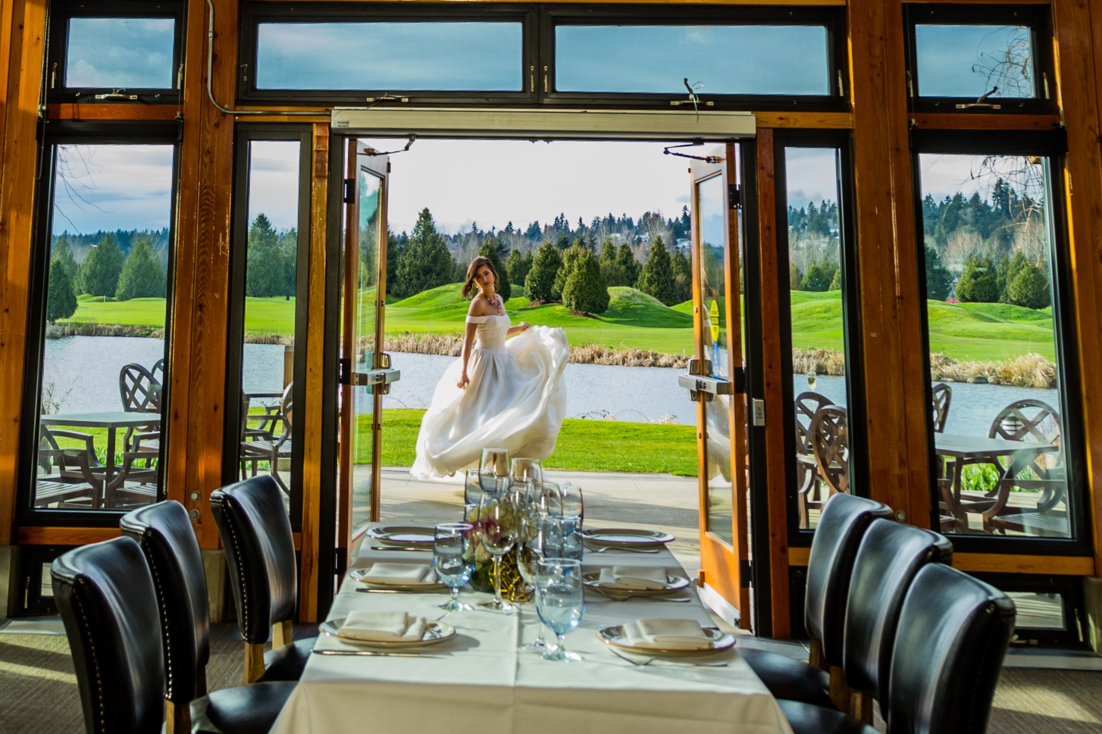 A bride stands in the doorway of the Riverway clubhouse overlooking the golf course