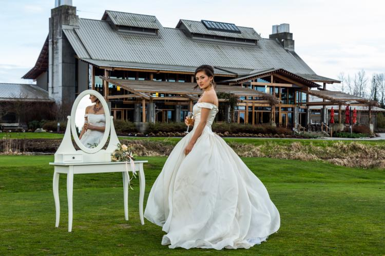 Bride posing for wedding photos with the luxurious Riverway clubhouse in the background