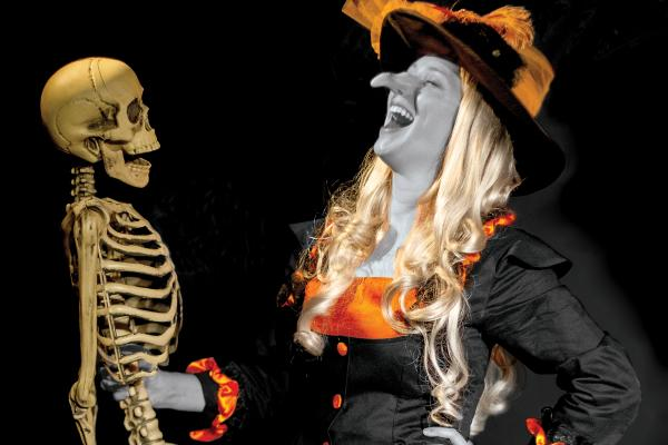 Fun witch laughing with skeleton
